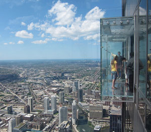 people in glass box over city